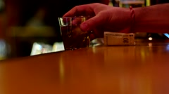 The man behind the bar takes whiskey and pays money for alcohol. - stock footage