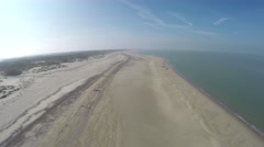 Stock Video Footage of Aerial flying over an empty quiet beach beautiful blue crisp sky 4k
