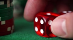 Red dice in hand and casino chips on green table Stock Footage