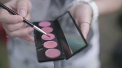 Girl holding a brush and cosmetics for make-up - stock footage