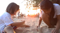 Brother and sister playing in sand and Light sunset behind Stock Footage