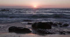 Sunrise over the ocean and rocks at a Cape Town beach Stock Footage