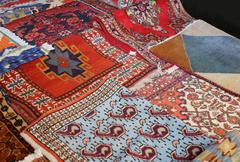 Many precious ancient colored wool rugs made by hand in the Middle East Stock Photos