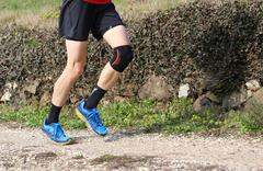 cross-country runner during the race with his knee wrapped by a knee brace - stock photo