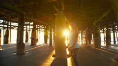 Woman Running on the Beach Under Pier at Sunset. Healthy Active Lifestyle. 4K - stock footage