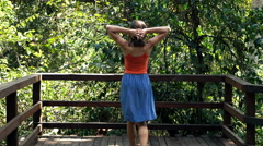 Woman walking out on terrace and stretching arms Stock Footage