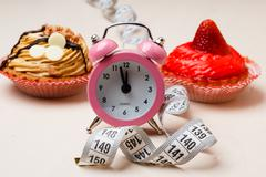 Sweet food measuring tape and clock on table - stock photo