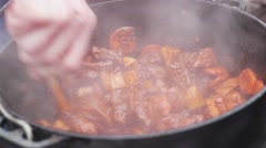 People Cook in the Camp. a Man Prepares a Stew of Meat and Ovoschey.on Gently - stock footage