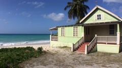 wide static shot of green beach house on Maxwell beach in Barbados - stock footage