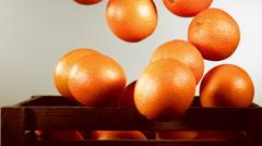 Ripe orange falls in the box Stock Footage