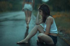 Sad woman in the rain. - stock photo