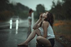 Woman in the rain and sad. - stock photo