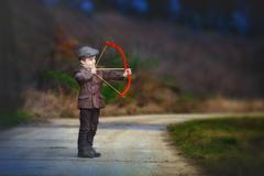 Adorable little preschool boy, shoot with bow and arrow at target in open air - stock photo