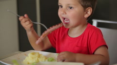 Boy dine sausage grill with potatoes - stock footage