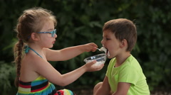 Girl feeding boy porridge from a spoon Stock Footage