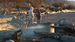 Young people at beach bonfire at sunset Stock Footage