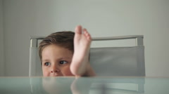 Little boy is sitting at the dining table - stock footage