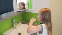 Girl brushing his teeth in the mirror - stock footage