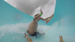 Happy young boy going down curved waterslide in slow motion Cape Town Stock Footage