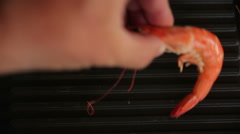 Hand puts the shrimp on the grill - stock footage