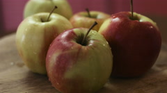 Close-up footage of fresh and wet green and red mixed apples lie on a wooden Stock Footage