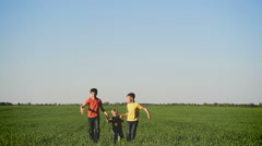 Happy young children  running around the field on nature - stock footage