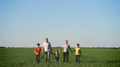 Happy young family with children  walking around the field Stock Footage