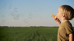Little boy blowing soap bubbles in summer park background. Stock Footage