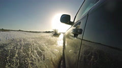Driving on muddy road with water splashes towards camera Stock Footage