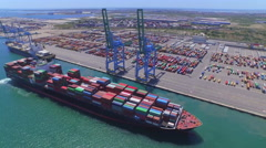 AERIAL: Fully loaded container ship docked at freight port terminal Stock Footage