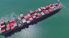 AERIAL: Flying around big freight container ship at sea - stock footage