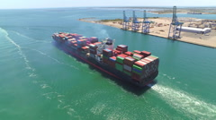 AERIAL: Container ship, loaded with shipping freight containers leaving port Stock Footage