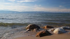 Surf, rocks mountains in the background Stock Footage