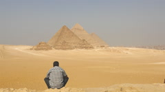 Egyptian sitting in front of  The Great Pyramids of Giza - Egypt Stock Footage