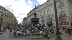 Tourists sitting around the iconic Shaftesbury Memorial Fountain in London Stock Footage