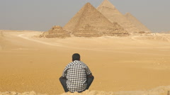 Zoom Out - Egyptian sitting in front of  The Great Pyramids of Giza - Egypt Stock Footage