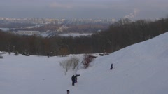 Kids Walking up the Hill to Ride a Sleigh Winter Hill Slope Right Bank of the - stock footage