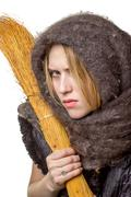 Angry woman in a scarf with a broom in his hand - stock photo