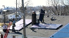 Roofers lift solar cell panels to house roof Stock Footage