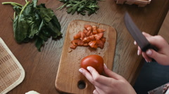 Woman slices a tomato for a salad on a kitchen wooden table,  vegetables Stock Footage