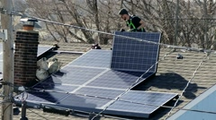 Roof worker installs solar cell power panels Stock Footage