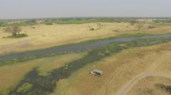 Tourist safari vehicle driving alongside water ways of the Okavango Delta Stock Footage