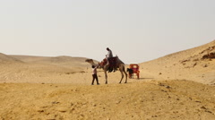Guide Hands Tourist on a Camel Water in the Desert-  Giza, Egypt - stock footage