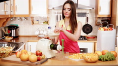 Woman making orange juice in juicer machine 4K Stock Footage