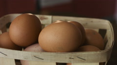 Close-up footage of basket of brown eggs lie on a wooden board which is spinning Stock Footage