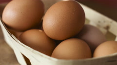 Brown eggs in a wooden basket spinning around on a table Stock Footage
