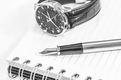 Black and white fountain pen on blank notepad and watch Stock Photos