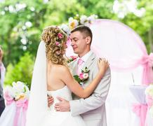 Happy newlywed romantic couple dancing at wedding aisle with pink decorations Stock Photos