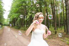 beautiful young woman with white wedding dress blowing bubble outdoors - stock photo