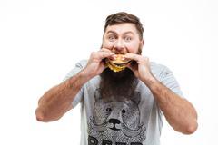 Hungry bearded young man eating hamburger - stock photo